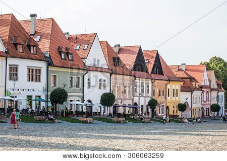 Bardejov, Slovakia - August 09, 2015: Tourists Sit On The Benches In The Sadow Of Old Main Square Bu