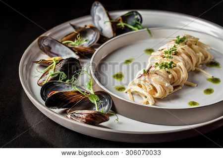 The Concept Of Italian Cuisine. Pasta With Cream Sauce, Pesto And Seafood, Mussels. European Cuisine