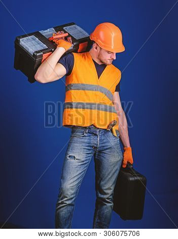 Repair Service Concept. Man In Helmet, Hard Hat Holds Toolbox And Suitcase With Tools, Blue Backgrou