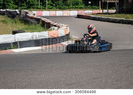 Young Racer At Go-kart Racetrack Circuit Championship. Racer With A Helmet Competing On Karting Race