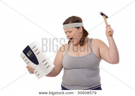 Angry fat woman punching scale by hammer, shouting.?