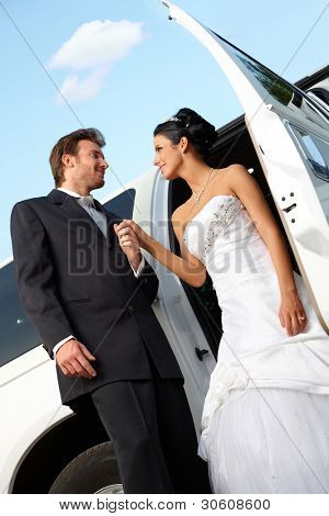 Bride and groom on wedding-day getting out of limousine.?