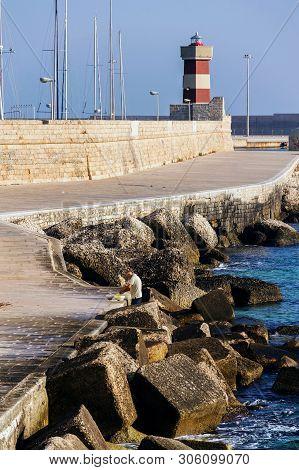 Monopoli, Italy - July 6 2018: Man Fishing In Front Of Lighthouse In Monopoli Port Near Castle Of Ca