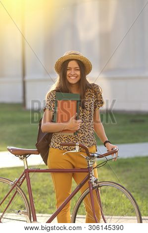 Young Female Student With Backpack And Books Riding A Retro Bicycle.female On Retro Bicycle. Young F