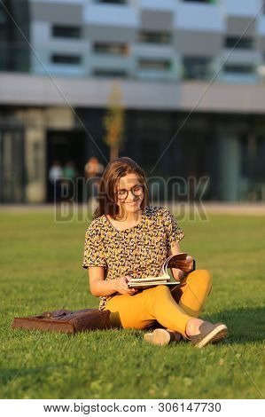 Young Female Student In Glasses With Backpack And Book Sitting On The Lawn. Young Female Have Lunch