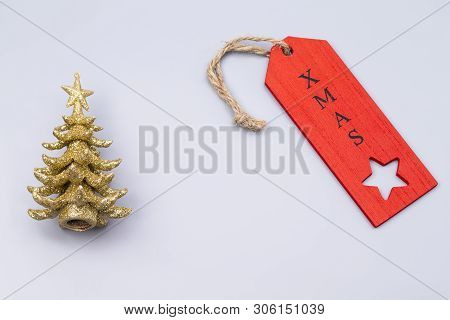 The Image Shows An Golden X-mas Tree With Red Label, Isolated On Grey