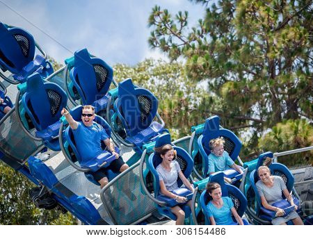 Family having fun riding a rollercoaster at a theme park. Screaming, laughing and enjoying a fun summer vacation together.