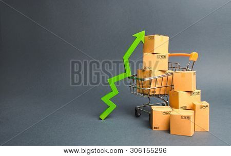 Shopping Cart With Cardboard Boxes And A Green Up Arrow. Increase The Pace Of Sales And Production O