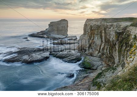 poster of Sunset over rocky coastline near Panther and Hole-In-The-Wall Beaches. Bonny Doon, Santa Cruz County, California, USA.