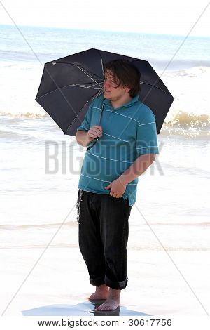 Serious Teen Boy With Umbrella In Surf