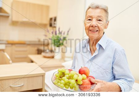 Senior woman with apple and grapes in senior citizen home or retirement home