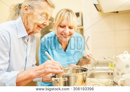 Nursing wife and senior citizen in the kitchen while cooking in assisted living
