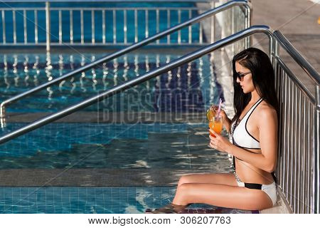 Beautiful Young Slim Woman With Long Dark Hair Wearing A White Swim Suit Is Leaning On The Metal Fen