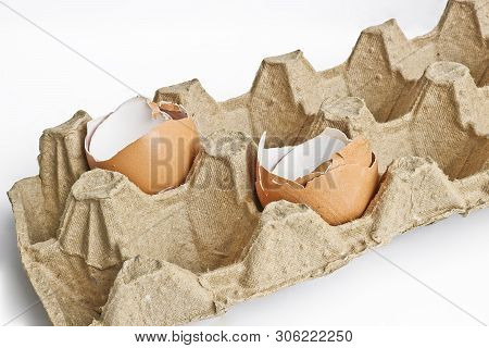 Carton packaging for eggs with broken eggshell on a light background. Organic concept poster
