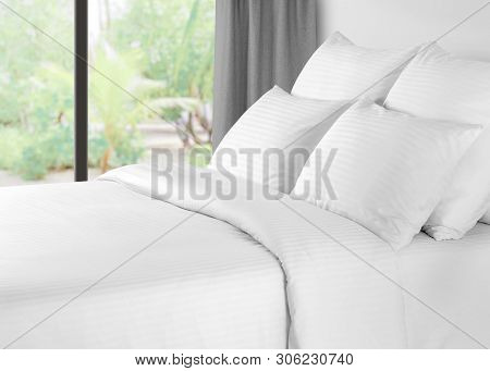 Bed With Linen Against A Window With Grey Curtains