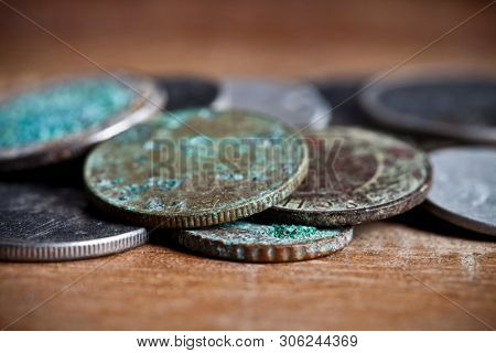 Pile of different ancient copper coins with patina ccloseup on rustic wooden table background.