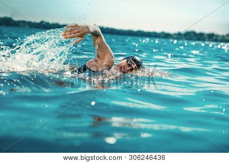 Professional Triathlete Swimming In Rivers Open Water. Man Wearing Swim Equipment Practicing Triathl