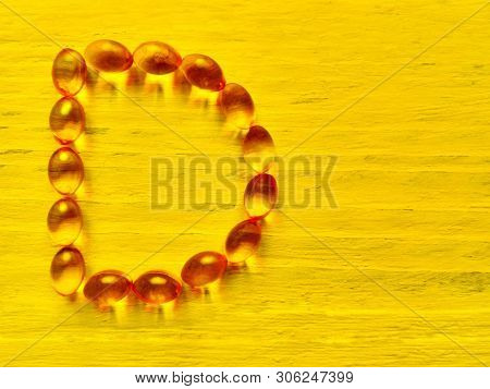 Vitamin D Capsule Pills In Alphabet Shape On Yellow Sun Background. Medicine Soft Gel Tablets Of Vit