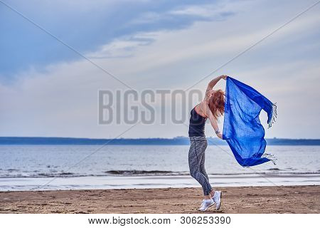 Slim Red-haired Middle-aged Woman In Sports Form Is Engaged In Dancing With A Blue Scarf. A Woman Is
