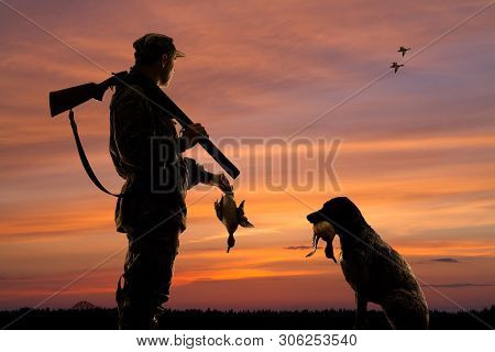 Silhouettes Of The Duck Hunter And His Dog With Downed Duck On The Sunset Background