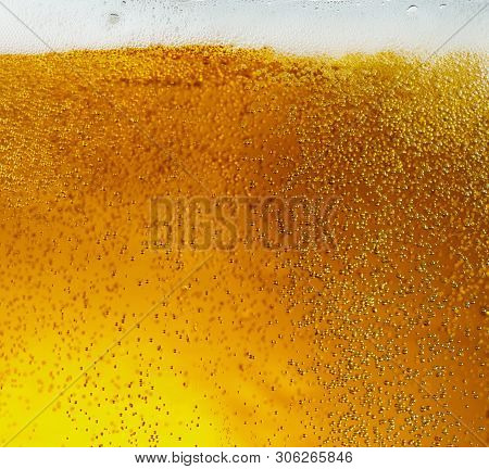 Close Up View Of Floating Bubbles In Light Golden Colored Beer Background. Texture Of Cooling Summer