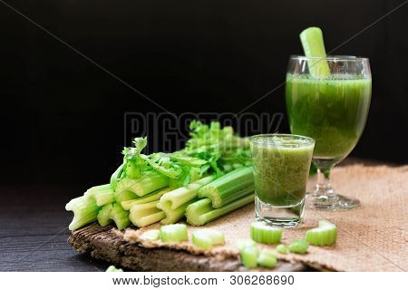 Blended Celery Juice In Welcome Drink Glass And Bunch Of Fresh Celery Stalk On Wooden Table With Lea