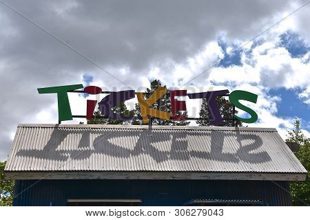 Colorful Letters Spell Out The Word T-i-c-k-e-t-s On The Roof Of A Building At An Amusement Park Thr