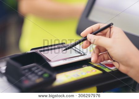 Close-up Of Consumer's Women Hand Signing On A Touch Screen Of Credit Card Sale Transaction Receipt
