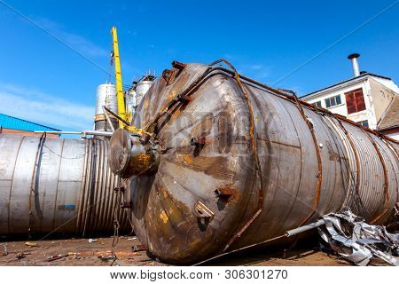 Obsolete Massive Old Metal Silos, Tanks Are Lain Down On The Ground, Waiting Cassation For Recycling