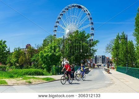 Gdansk, Poland - June 2, 2019: People on the bike trip at the ferris wheel in Gdansk, Poland. Gdansk is the historical capital of Polish Pomerania with medieval old town architecture.