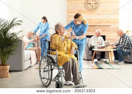 Nurse Giving Glass Of Water To Elderly Woman In Wheelchair At Retirement Home. Assisting Senior Peop