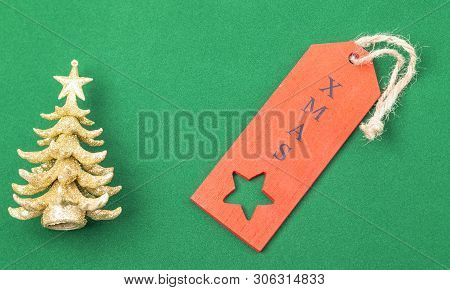 The Image Shows An Golden X-mas Tree With Red Label, Isolated On Green