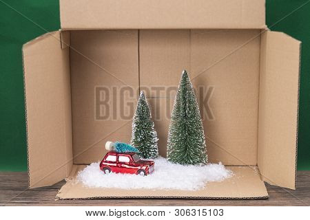 A Symbolic Photo Consisting Of A Model Car, Some Trees And Artificial Snow In An Open Box