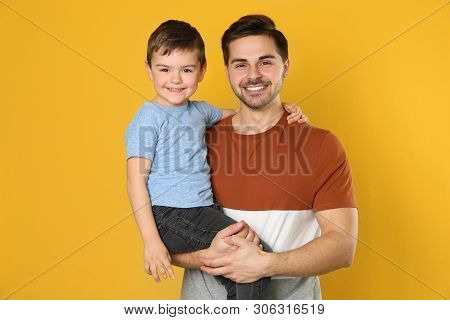 Portrait Of Dad And His Son On Color Background