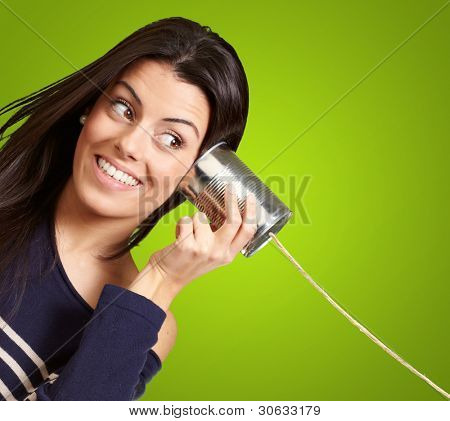 Young woman hearing using a metal tin can over green background