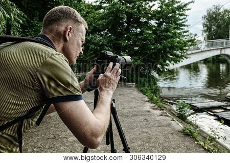 The Photographer Is Photographing With A Tripod. He Is Adjusting The Camera.