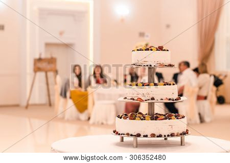 Three Story Wedding Cake With Berries In The Hall With Blurry Guests On The Background