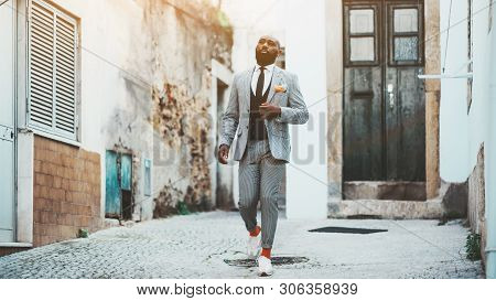 An Elegant Bald Bearded African Man In A Fashion Costume With Tie And Orange Socks Is Walking Down T