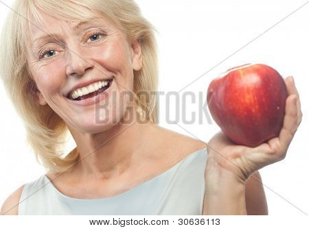 portrait of attractive  caucasian smiling mature woman blond isolated on white studio shot with red apple