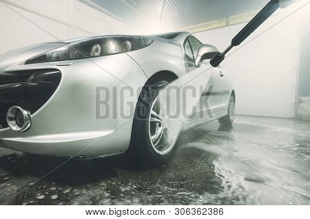 Man Cleaning Vehicle With High Pressure Water Spray Or Jet. Car Wash Details. Wash The Wheels With W