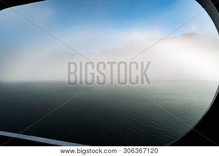 Obscured Foggy View Of Alaska Glacier Bay Mountain Range Through Cruise Ship Window Port Hole Sailin