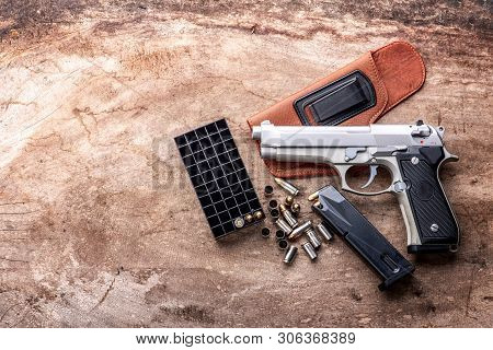 9 mm pistol gun bullets and magazine   strewn on the wooden background top view
