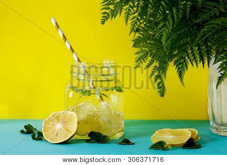 Lemonade With Fresh Lemon. Summer Drink. Infused Detox Water In Mason Jar On Yellow Background. Deto