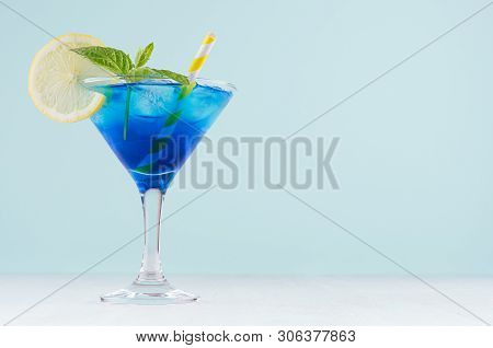 Summer Cold Blue Lagoon Drink With Ice Cubes, Lemon Slice, Yellow Straw, Green Mint In Elegant Wine