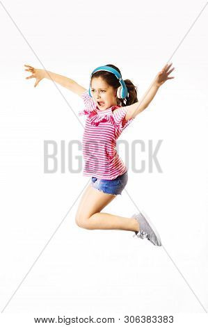 Little Jumping And Shouting Little Caucasian Girl With A Headphones