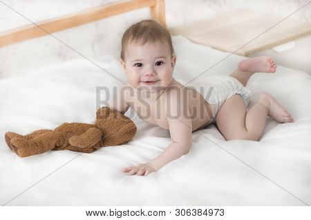 Cheerful Baby Boy Girl In A Diaper Lying With A Teddy Bear. Cute Baby In A Diaper Crawling On The Be