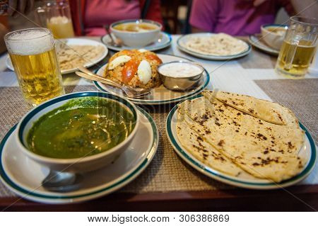 Typical Nepalese Meal And Beer In Pokhara Restaurant, Himalayas, Nepal. Assorted Indian Nepalese Foo
