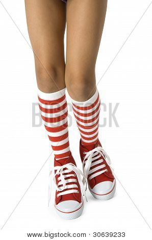 Young girls legs wearing long red striped socks with red shoes on a white background. Clipping path