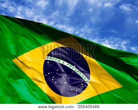 Waving Flag Of Brazil Close Up Against Blue Sky