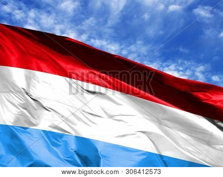 Waving Flag Of Luxembourg Close Up Against Blue Sky
